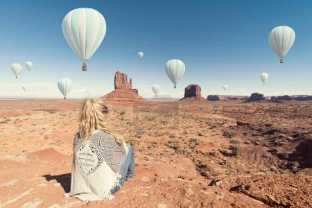 woman sitting in Monument Valley with hot ballons overview