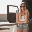 Surfer girl sitting at a car with surfboard. calif...