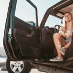 Surfer girl sitting in car at the beach. californi...