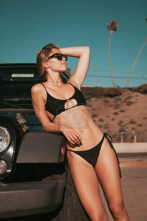 Surfer girl standing by a car on parking spot. cal...