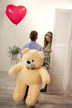 Boy teen gives a girl a teddy bear with a ball in the form of a red heart