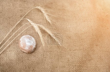 gingerbread and wheat spikelets on burlap in the sunlight