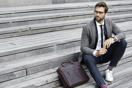 Handsome businessman sitting on staircase