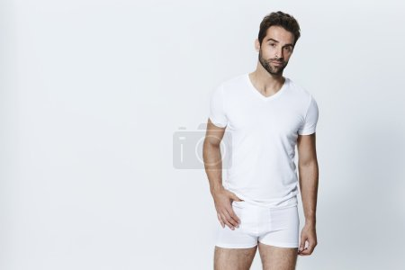 Photo for Man wearing white t-shirt and underpants posing in studio - Royalty Free Image