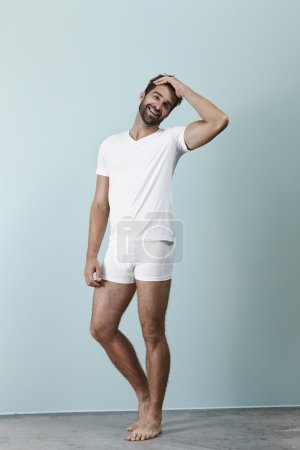 Photo for Portrait of handsome man laughing in white underwear - Royalty Free Image
