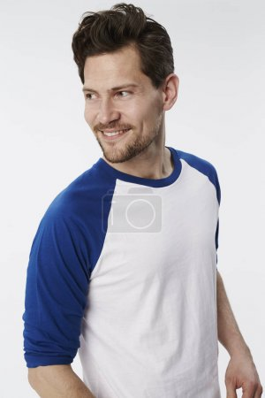 Smiling man in white and blue sweatshirt