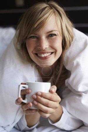 Woman with coffee cup in bed