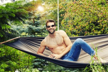 Shirtless man in hammock