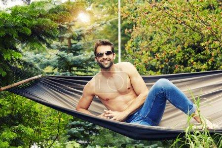 Photo pour Homme torse nu dans hamac regardant la caméra et souriant - image libre de droit