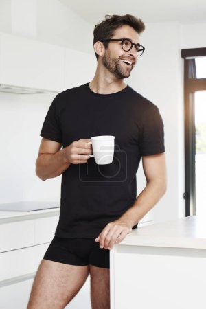 Photo for Handsome bearded man in black t-shirt with coffee cup posing in kitchen - Royalty Free Image