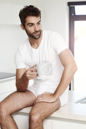 Man in underwear sitting with coffee cup