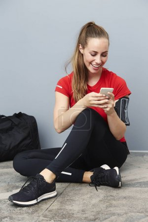 Smiling athletic woman with cell phone
