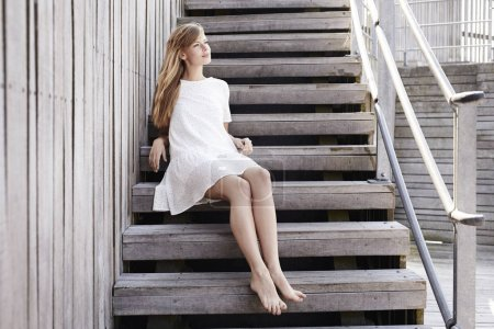 Photo for Barefoot beautiful woman sitting on steps and smiling - Royalty Free Image
