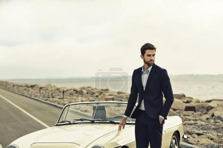 Suited man with vintage car
