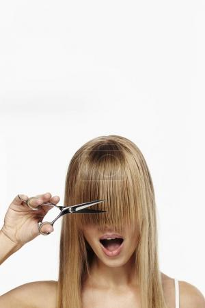 Blond girl with scissors