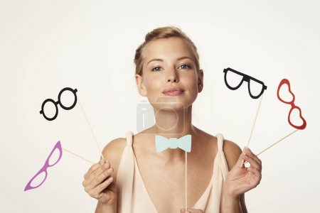 Woman holding bow tie and glasses