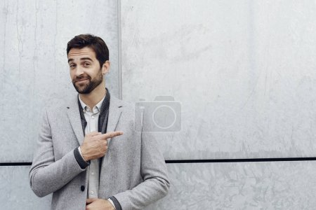 Guy in grey overcoat pointing