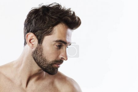 Photo for Handsome shirtless man in profile looking away, studio - Royalty Free Image