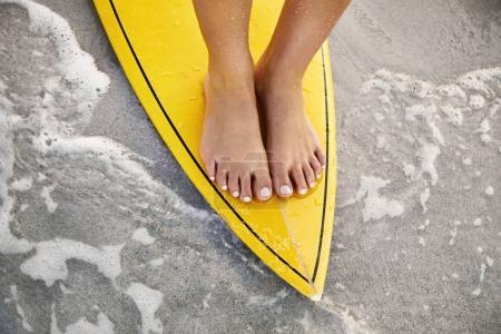 Barefoot girl on surfboard