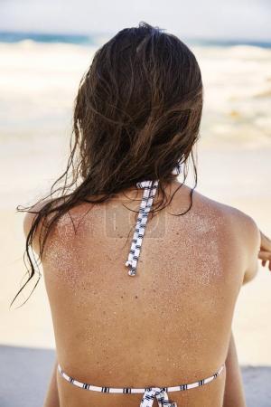 Woman in bikini sitting on beach
