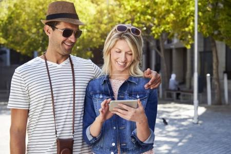 Tourist couple using tablet