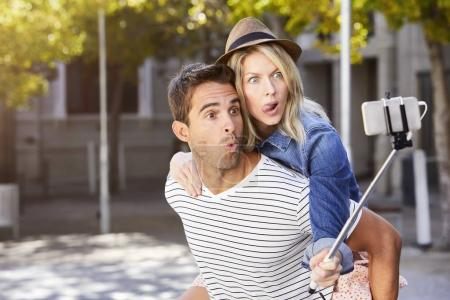 couple doing piggyback for selfie