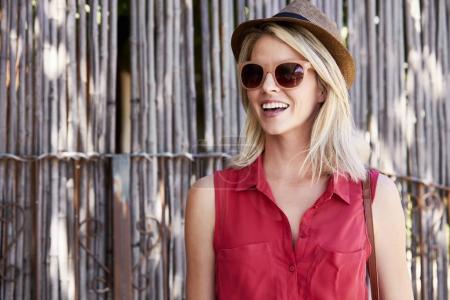 Photo pour Glamour jeune femme en lunettes et chapeau souriant et détournant les yeux - image libre de droit