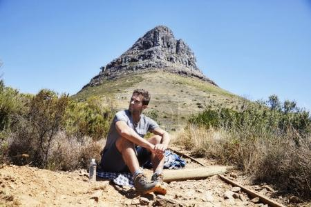 hiker relaxing while sitting on ground