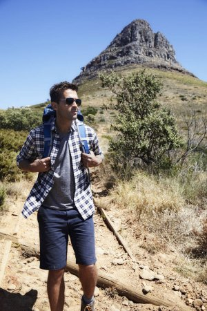 Young man hiking on trail from mountain