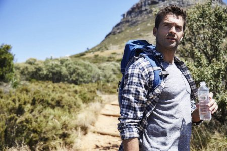 Photo for Hiker in checked shirt on trail with water bottle, side view - Royalty Free Image