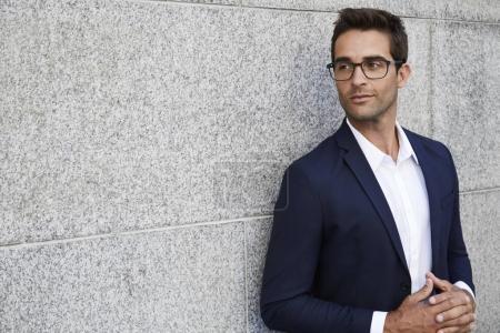 Photo pour Homme d'affaires réfléchi en costume et lunettes, détournant les yeux - image libre de droit