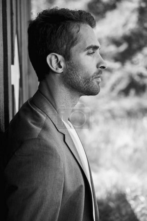 handsome guy with stubble standing outdoors