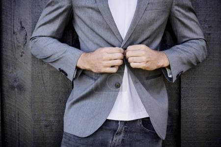 Guy in jeans buttoning suit jacket