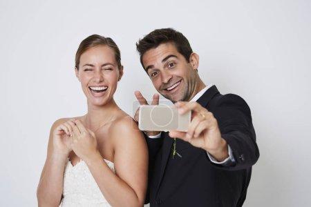 Bride and groom taking selfie on smartphone
