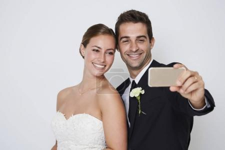 Bride and groom taking selfie on smartphone