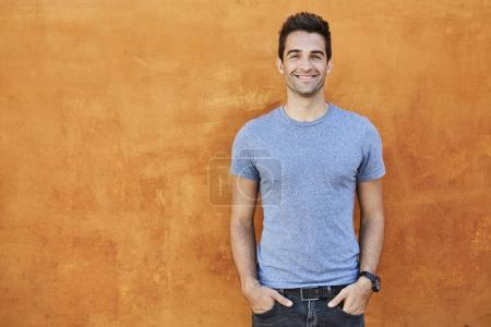 Photo for Smiling guy in blue t-shirt against orange wall - Royalty Free Image