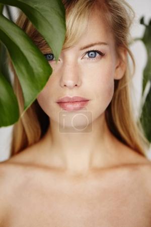 woman looking through leaf