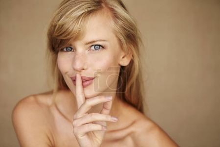 blond woman with finger on lips