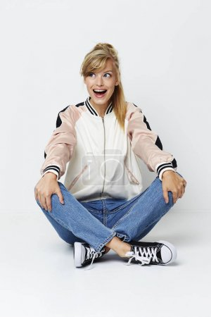 Photo for Excited girl in jacket and jeans sitting on floor - Royalty Free Image