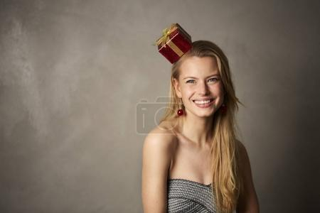 Portrait of young woman with gift on head smiling at camera