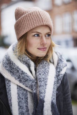 Portrait of young woman in pink hat and scarf looking aside