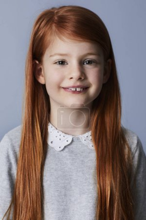 Portrait of smiling redheaded girl smiling at camera