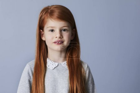 Portrait of smiling redheaded girl looking at camera