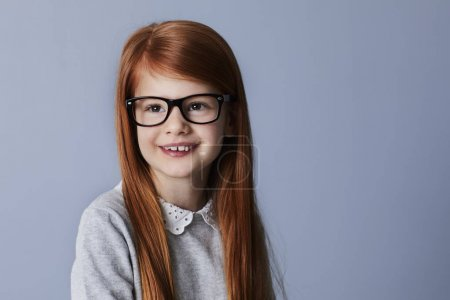 Portrait of smiling redhead girl in glasses, looking away