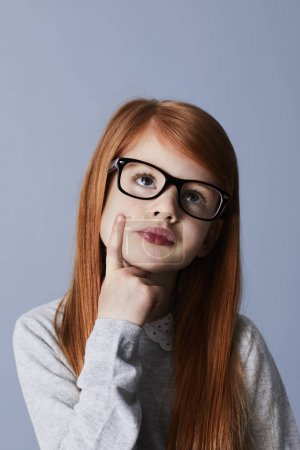 Portrait of redheaded pensive girl wearing glasses