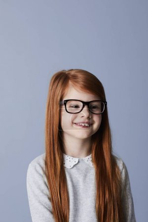 Smiling redheaded girl in glasses looking aside