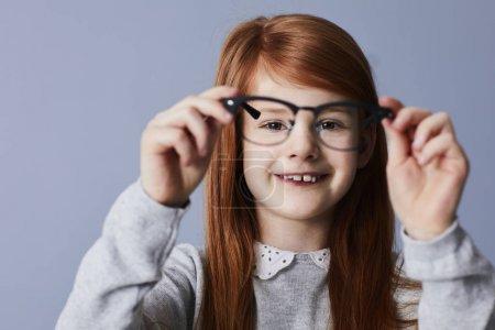 Redheaded girl holding up glasses, portrait