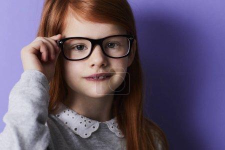 Redheaded girl adjusting glasses looking at camera, portrait