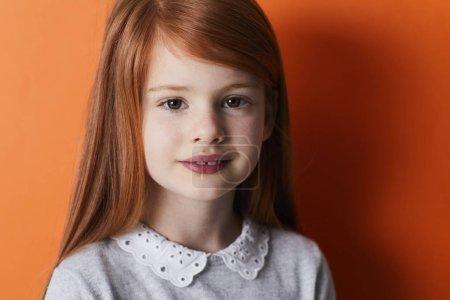 Cute redheaded kid smiling at camera, portrait