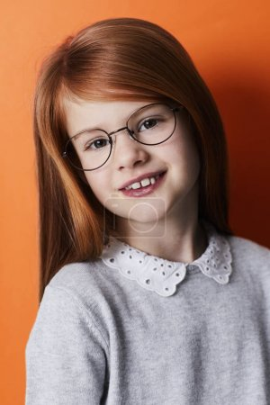 Portrait of redheaded girl smiling at camera in glasses